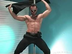 Sexy stud in police officer costume is dancing for his pal.