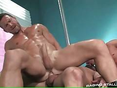 Muscled man jumps on buddy`s shaft while other guy waits for his turn.