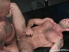 Two muscled tattooed guys are thoroughly fucking.